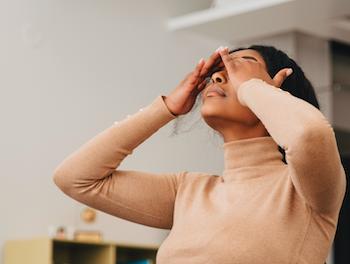 Mujer sentada en el escritorio con las manos presionadas contra la cabeza en dolor