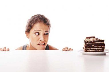 Woman glancing at a slice of chocolate cake