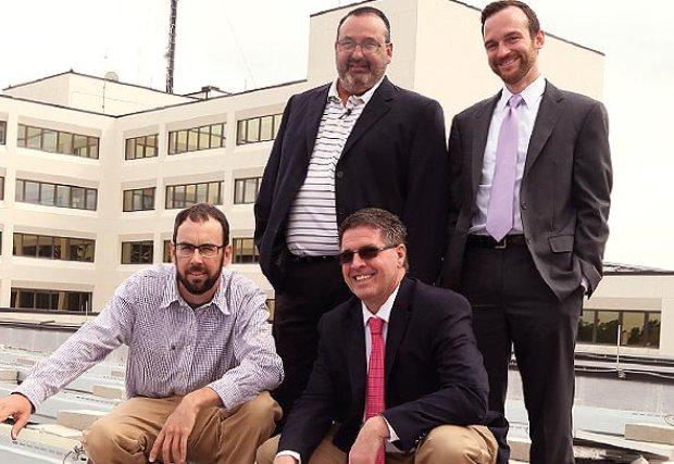 Chris Howard, de Southern View Energy, demuestra al CEO Vance Reynolds, Ray Hoyer y al COO Matt Merrifield cómo funcionan los paneles solares.