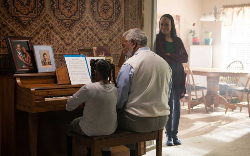 Grandfather playing piano with granddaughter as adult daughter watches